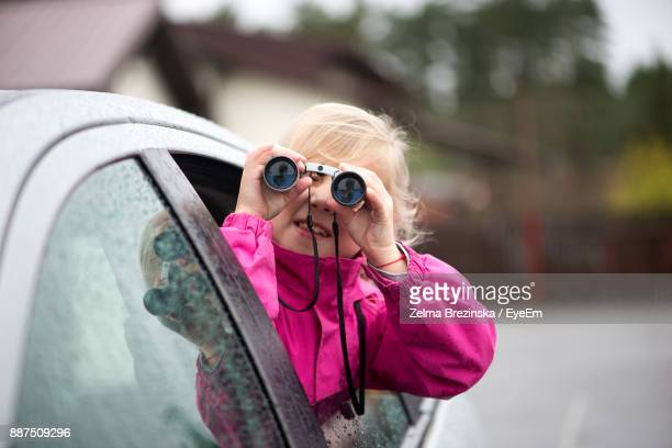 Sid View Of Girl Looking Through Binoculars While Traveling In Car