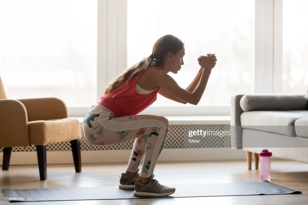 Side full-length view woman wearing activewear makes deep squat : Stock Photo