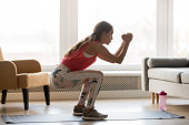 Side full-length view woman wearing activewear makes deep squat