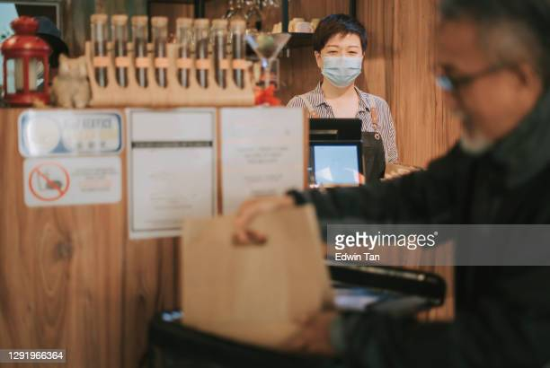 side hustle asian chinese senior man delivery picking up take away food and putting inside thermo bag at cafe - religious service stock pictures, royalty-free photos & images