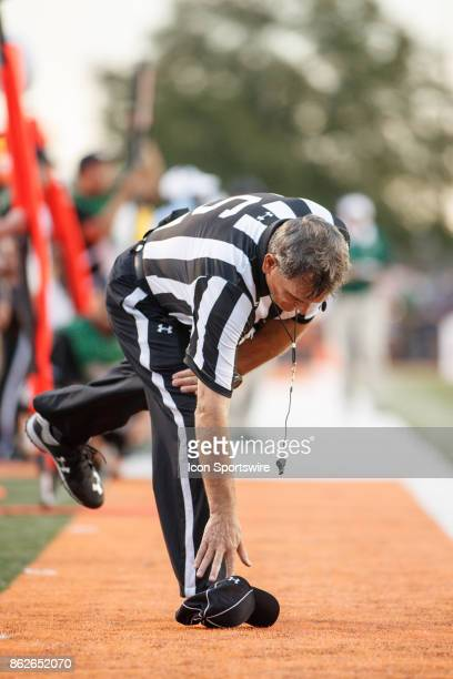 Side judge Arthur Lucky picks up his dropped hat in the second half of a game between the Ohio Bobcats and the Bowling Green Falcons on October 14th...