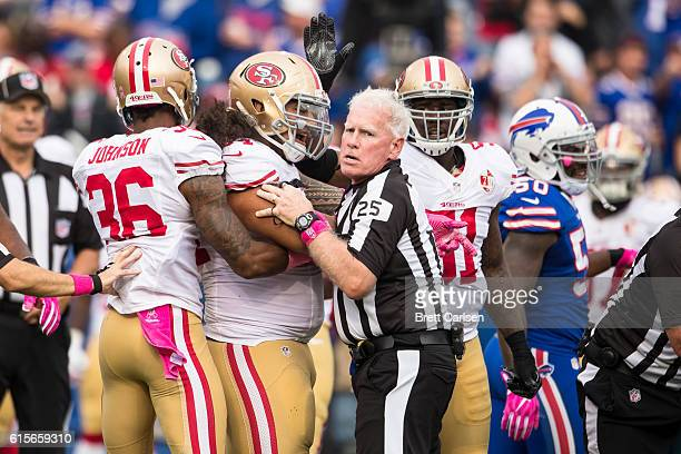 Side judge Bob Waggoner attempts to hold back members of the San Francisco 49ers during the game against the Buffalo Bills on October 16 2016 at New...