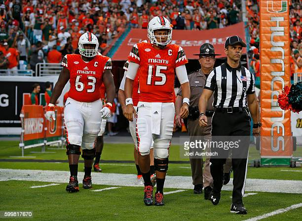 Side judge Eddie Bonet walks out with Brad Kaaya and Danny Isidora of the Miami Hurricanes prior to the game against the Florida AM Rattlers on...