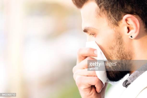 Seite der Ansicht schöner Mann ist Blowing Nase mit Bokeh Hintergrund