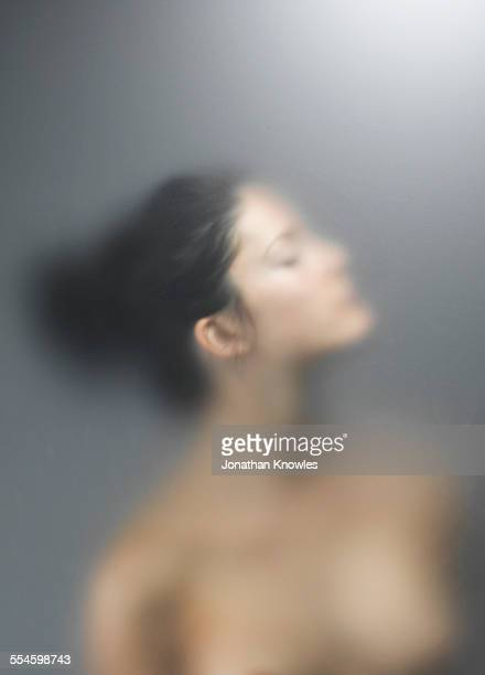 Side portrait of nude female behind frosted glass