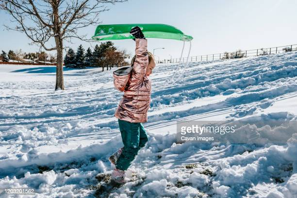 side portrait of young girl carry sled up a snowy hill - froid humour photos et images de collection