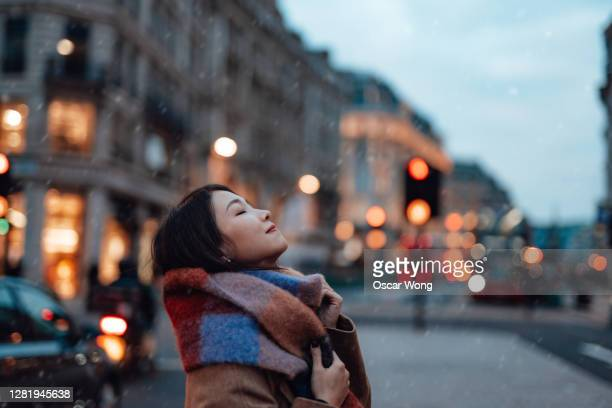 side portrait of young woman with scarf on the city street - travel stock pictures, royalty-free photos & images