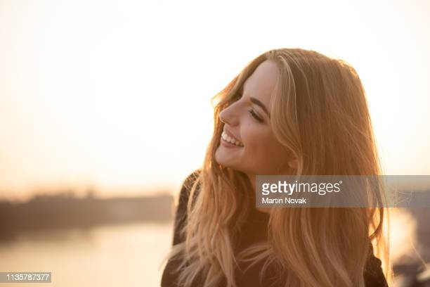 side pose of beautiful woman at sunset - woman flashing stock photos and pictures