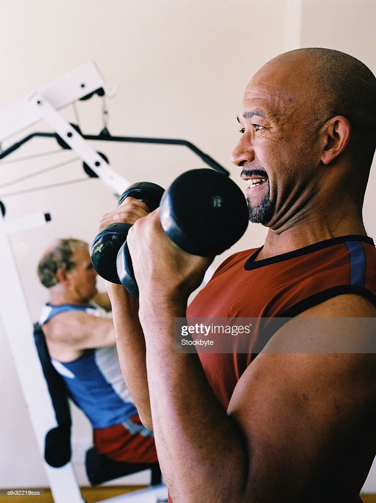 side profile close-up of a man working out with dumbbells in a gym : Stock Photo