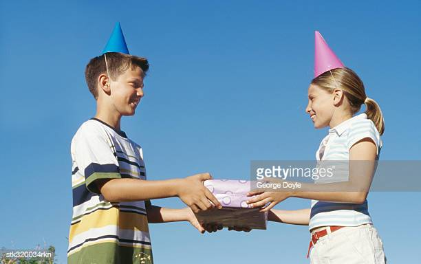 side profile of a boy and a girl holding a gift