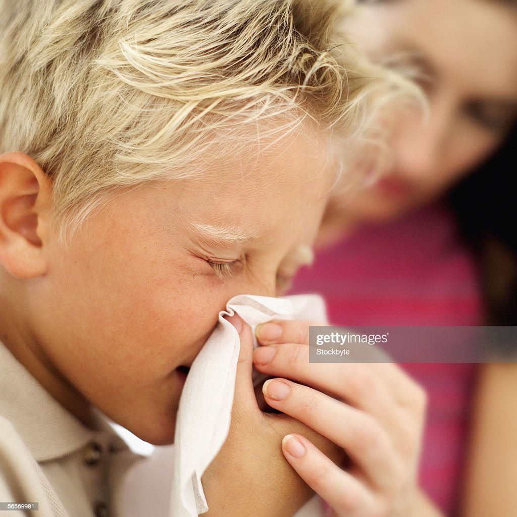 side profile of a boy blowing his nose : Stock Photo