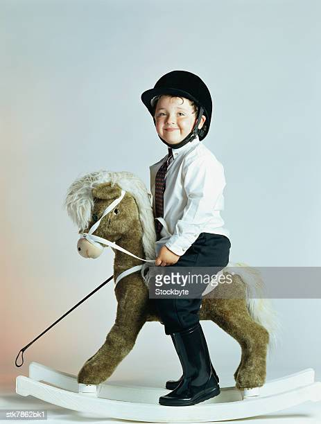 side profile of a boy (6-8) riding a rocking horse