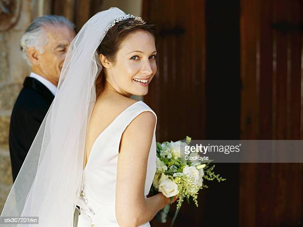 side profile of a bride and her father entering a church