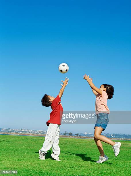 side profile of a brother and his sister playing with a soccer ball