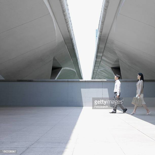 Side profile of a businessman and a businesswoman walking