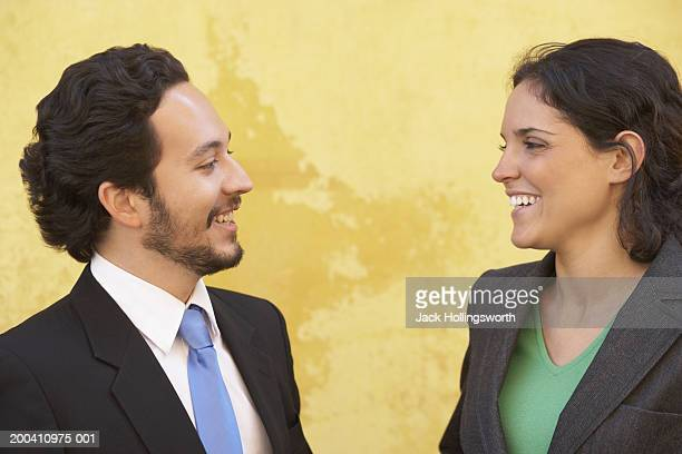 Side profile of a businessman and businesswoman smiling at each other