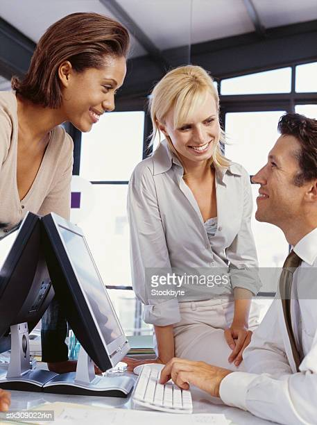 side profile of a businessman and two businesswomen in an office