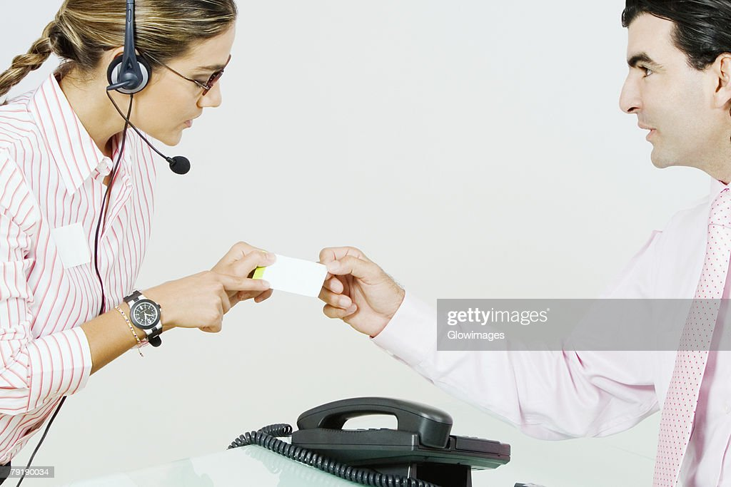 Side profile of a businessman giving a business card to a receptionist : Foto de stock