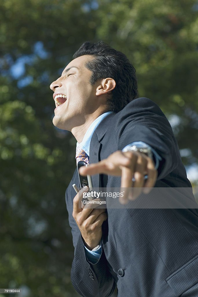 Side profile of a businessman holding a mobile phone and laughing : Foto de stock