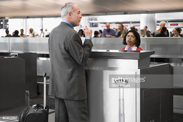 Side profile of a businessman standing at a ticket counter in an airport