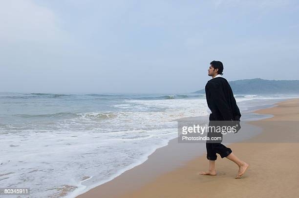 side profile of a businessman walking on the beach - rolled up trousers stock pictures, royalty-free photos & images