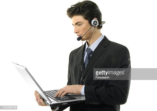 Side profile of a businessman wearing a headset and using a laptop