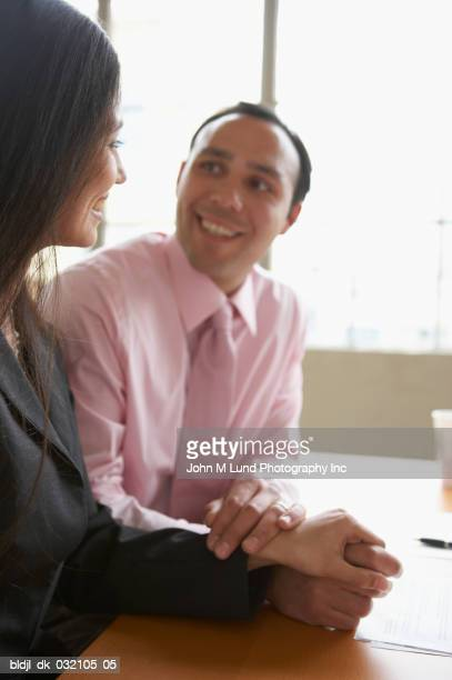 Side profile of a businesswoman and a businessman holding hands in an office