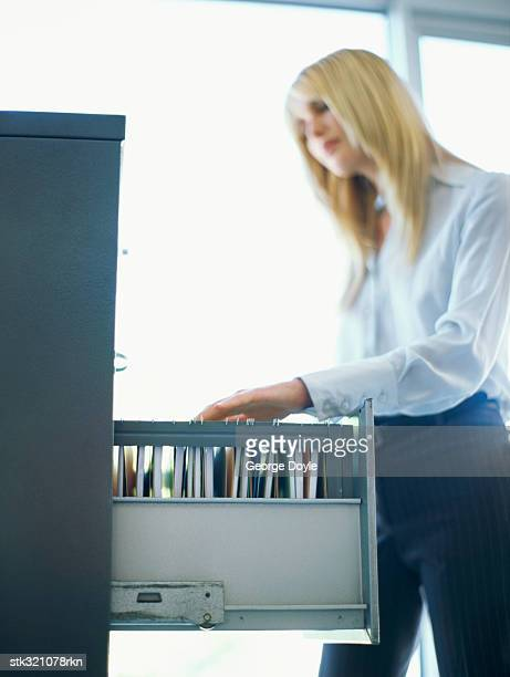 side profile of a businesswoman at a filing cabinet in an office