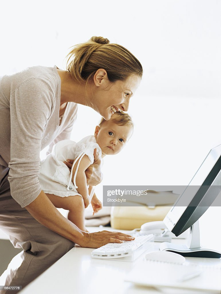 side profile of a businesswoman carrying her daughter and using a computer : Stock Photo
