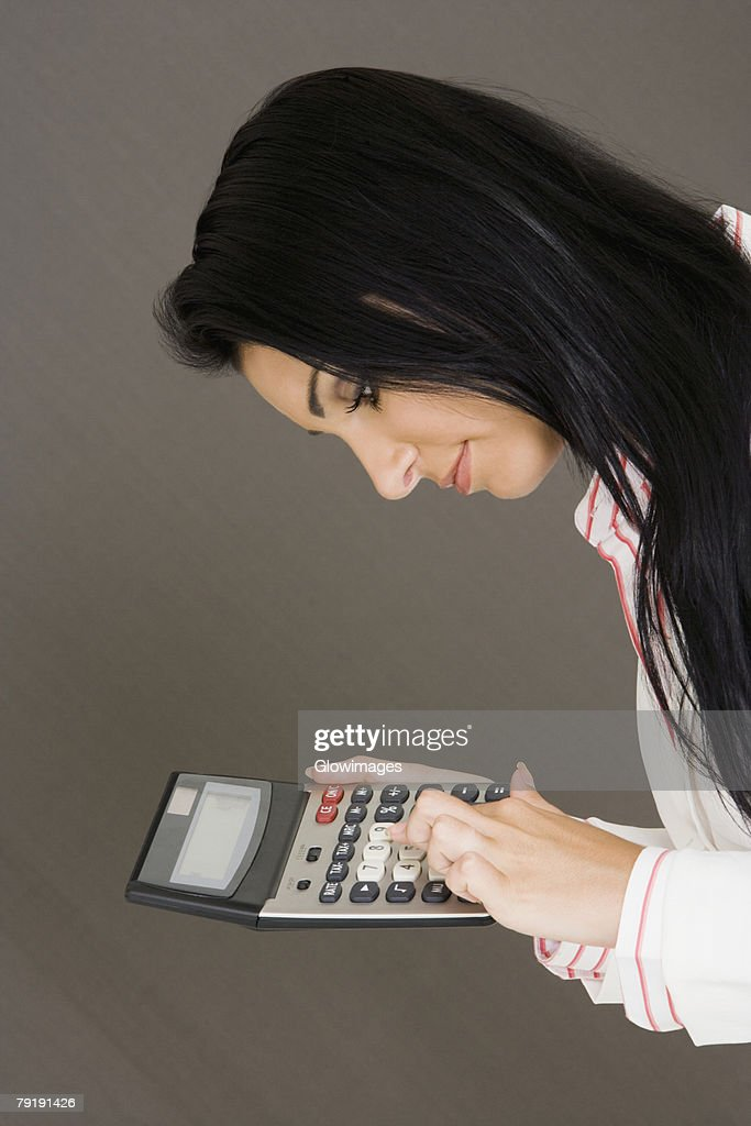 Side profile of a businesswoman holding a calculator : Foto de stock