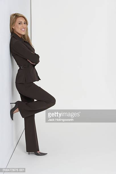 Side profile of a businesswoman leaning against a wall