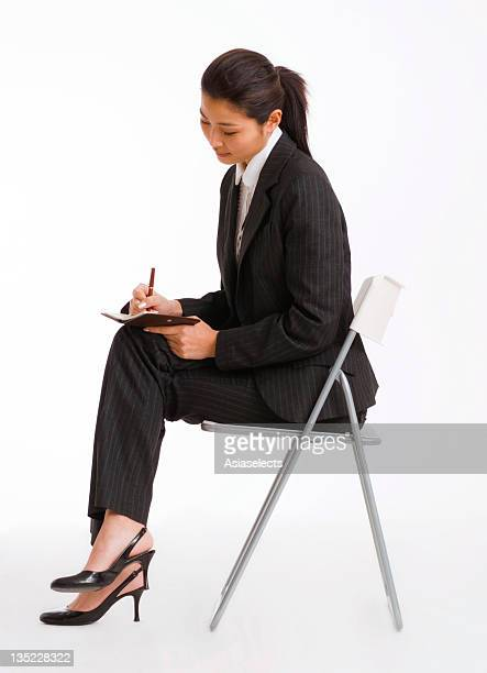 Side profile of a businesswoman sitting on a chair and writing in a diary