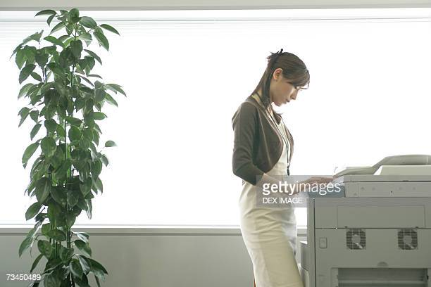 Side profile of a businesswoman using a photocopier