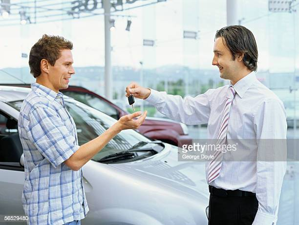 side profile of a car dealer giving car keys to a young man