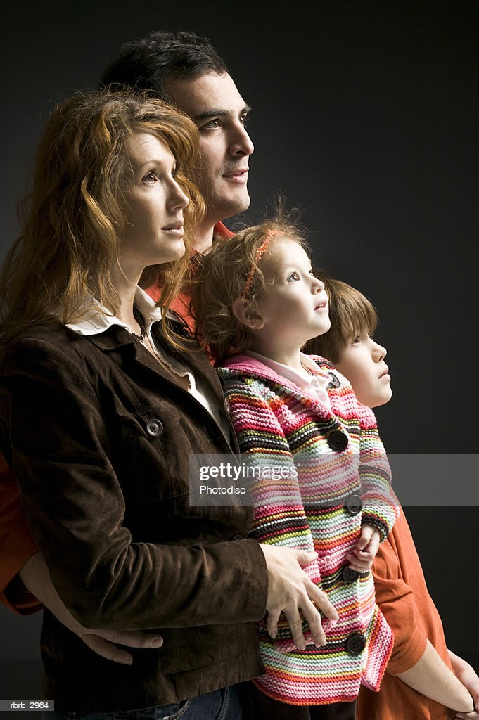 Side profile of a father and mother with their children : Stock Photo
