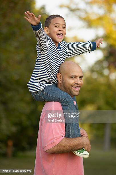 side profile of a father carrying his son on his shoulders - long sleeved stock pictures, royalty-free photos & images