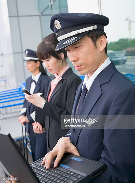 Side profile of a female cabin crew holding a mobile phone and standing with two pilots at an airport