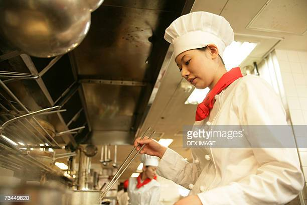 Side profile of a female chef cooking in the kitchen