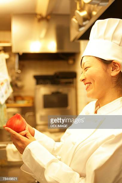 Side profile of a female chef holding a tomato and smiling