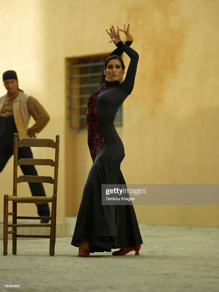 Side profile of a female dancer dancing with a young man in the background : Stock Photo