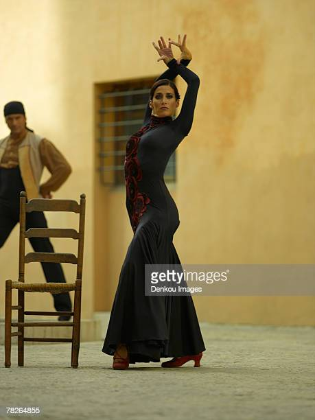 side profile of a female dancer dancing with a young man in the background - flamenco dancing stock photos and pictures