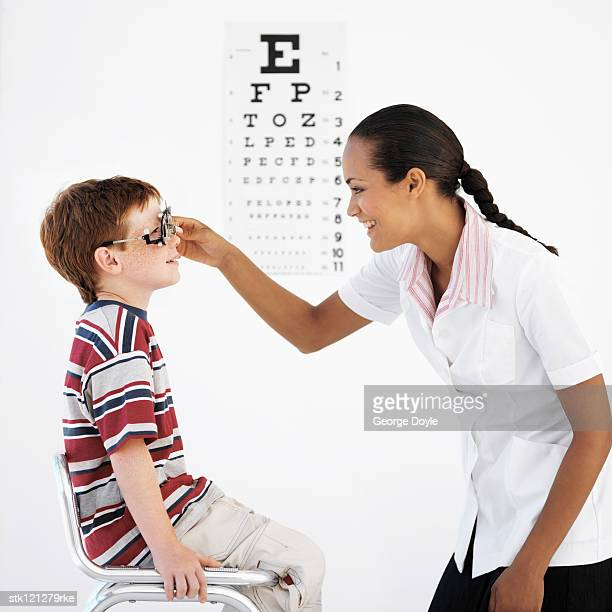 Side profile of a female optometrist examining a boy's (8-10) eyes