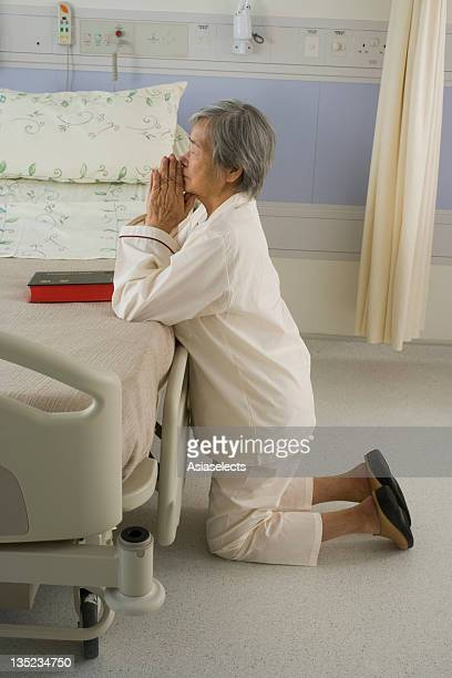 Side profile of a female patient praying beside a bed in the hospital