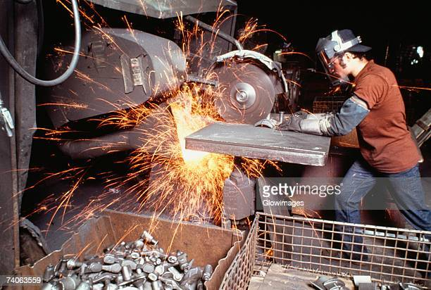 Side profile of a foundry worker working on a metal saw in a factory, Wisconsin, USA
