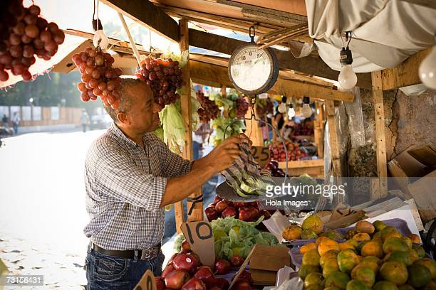 Side profile of a fruit seller weighing fruit, Santo Domingo, Dominican Republic
