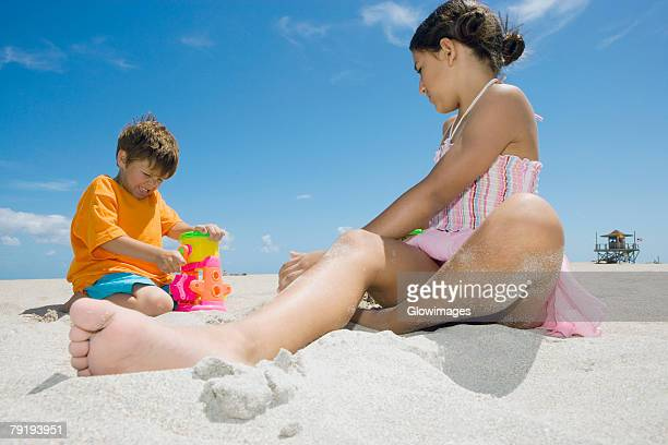 Side profile of a girl and a boy playing on the beach
