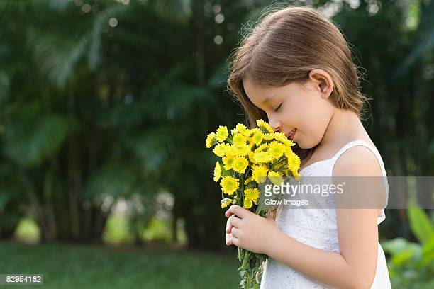 side profile of a girl holding a bunch of flowers and smelling - long stem flowers stock pictures, royalty-free photos & images