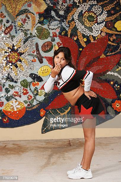 Side profile of a girl posing in front of a mosaic wall