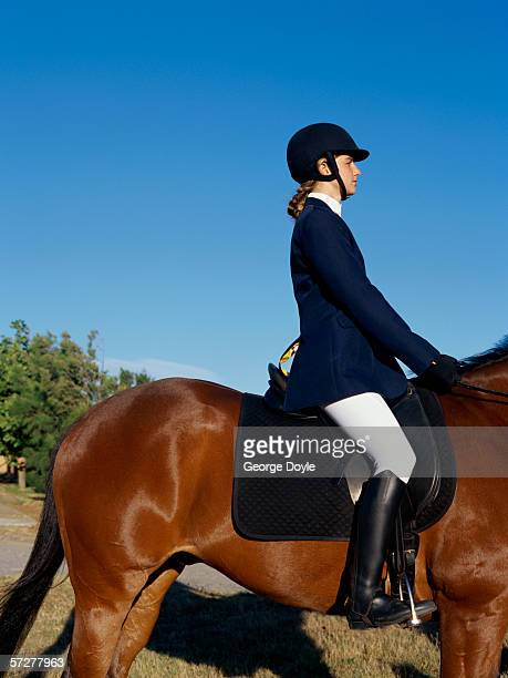 side profile of a girl riding a horse - equestrian helmet stock pictures, royalty-free photos & images