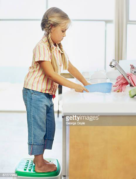 Side profile of a girl washing dishes